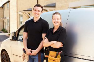 Portrait of male and female trade workers by a van