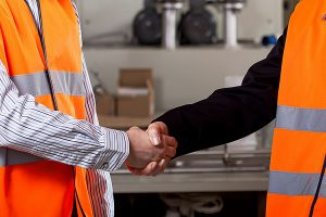 two people in hi-vis vests shaking hands